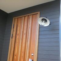 重厚感のある木目の扉とアンティークな照明の玄関